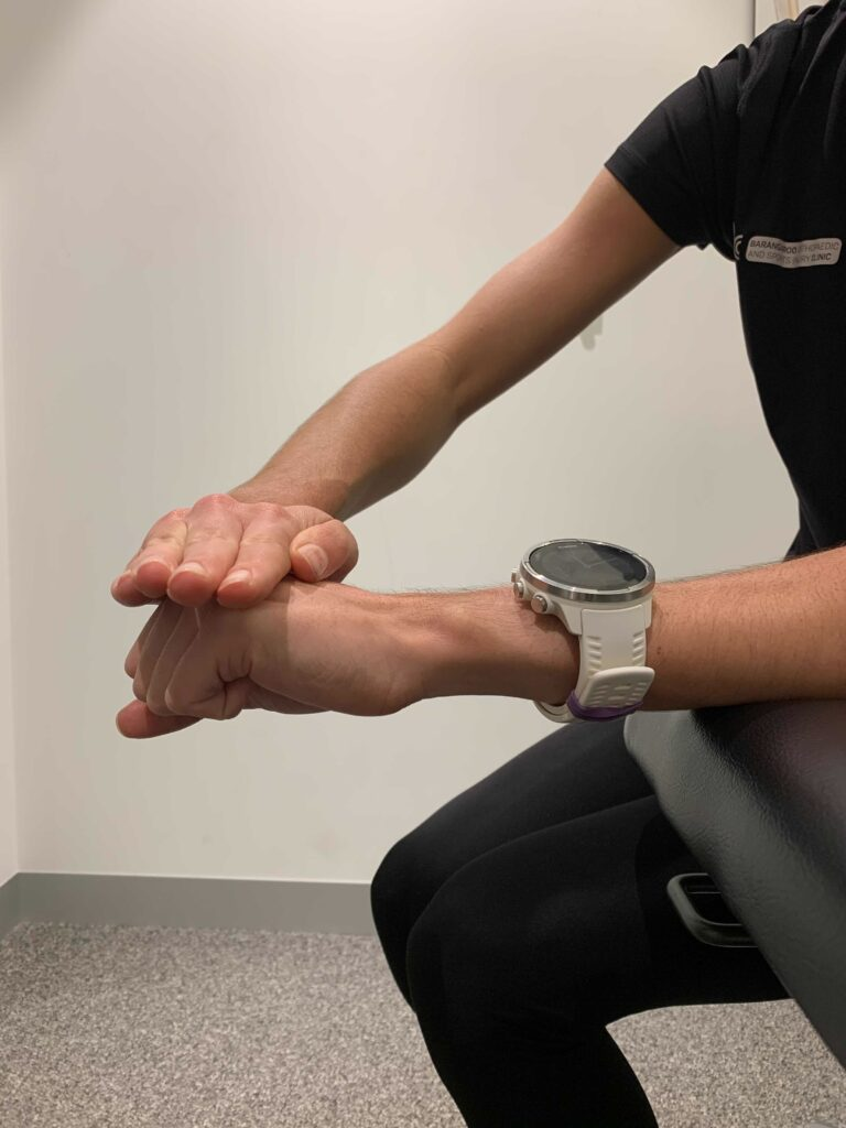 Woman demonstrates an isometric wrist extension to treat tennis elbow