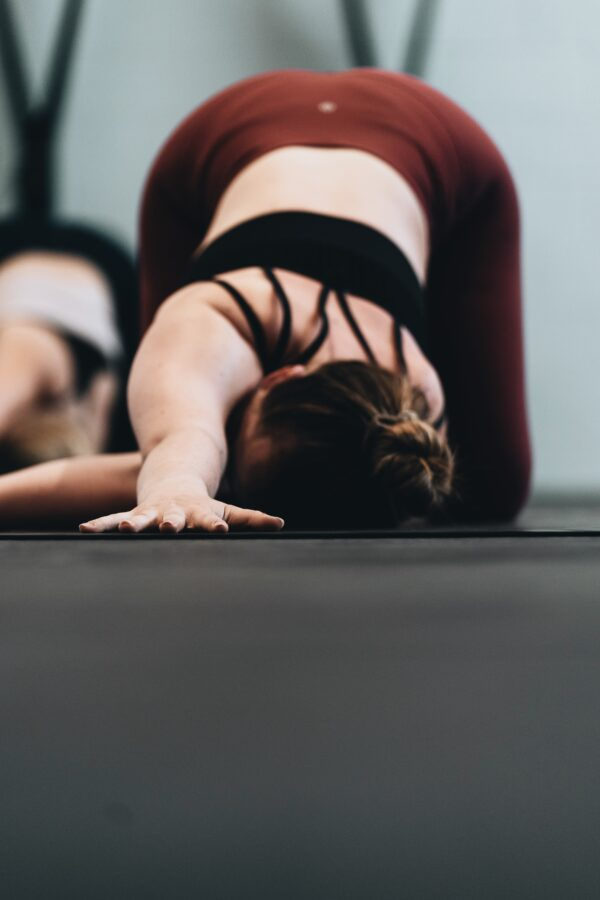 woman in a puppy yoga pose with her arm threading the needle